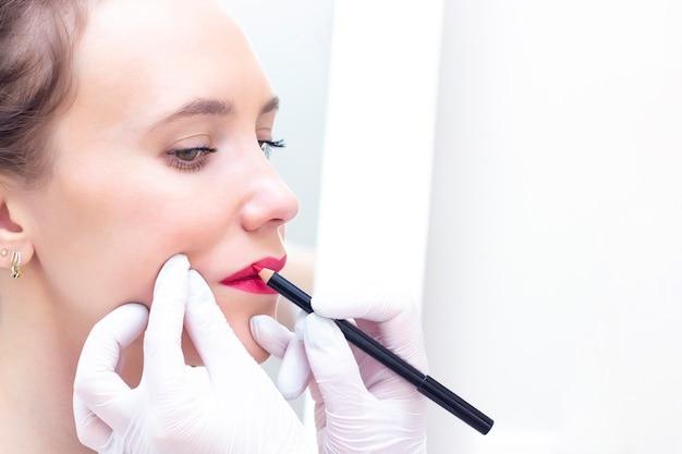 Молодая женщина, имеющая перманентный макияж на губах в салоне косметологов. Premium Фотографии