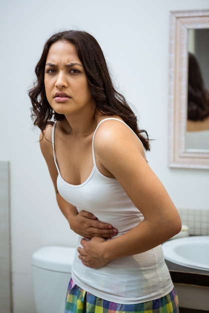 Young woman having stomach pain in bathroom | Premium Photo