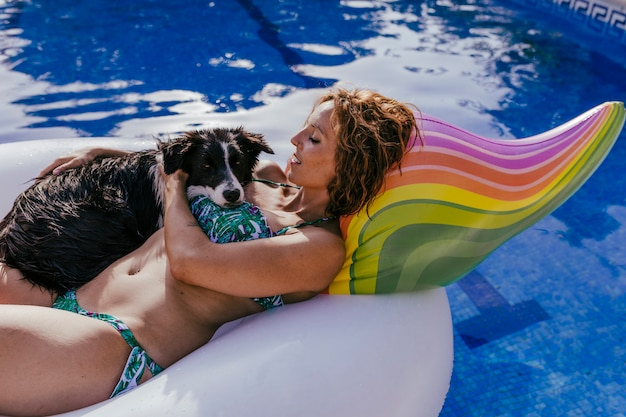 Young woman and her border collie dog standing on an inflatable toy unicorn at the swimming pool Premium Photo