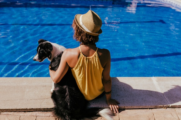 Young woman and her border collie dog at the swimming pool Premium Photo
