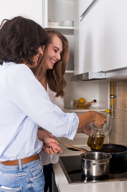 Young woman and her friend together preparing the food in the kitchen Free Photo