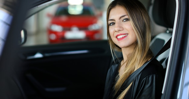 Young woman in her new car smiling Premium Photo