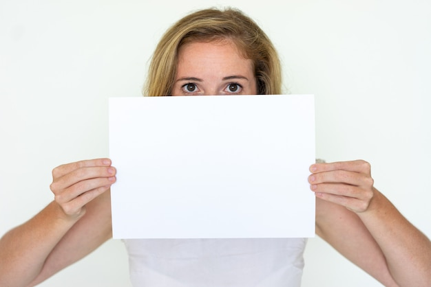 Young woman hiding behind blank sheet of paper Free Photo