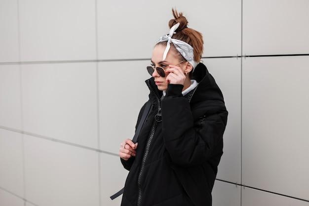 야외에서 흰 벽 근처에 검은 선글라스에 트렌디 한 두건에 세련된 헤어 스타일이있는 가죽 배낭과 세련된 긴 재킷에 젊은 여성 소식통. 미국 소녀. 현대 패션. 프리미엄 사진