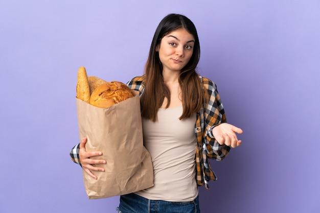 肩を持ち上げながら疑わしいジェスチャーを作る紫色の壁に隔離されたパンでいっぱいのバッグを保持している若い女性 Premium写真