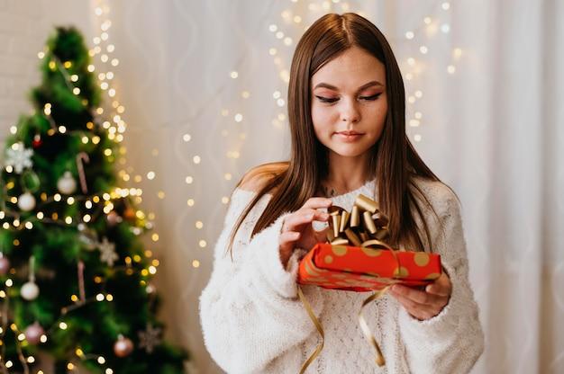 Молодая женщина, держащая елку в помещении Бесплатные Фотографии
