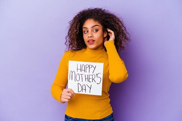 ゴシップを聞いて孤立した幸せな母の日のプラカードを保持している若い女性 Premium写真