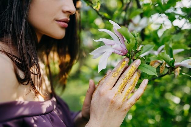 Молодая женщина, держащая цветок магнолии в парке. Premium Фотографии