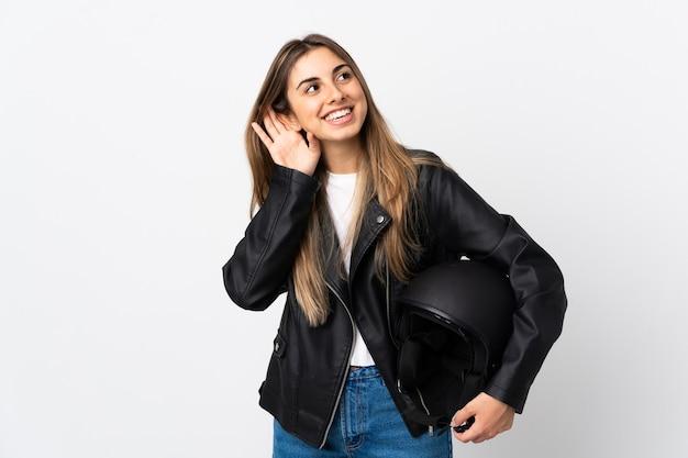 何かを聞いて孤立した白い壁にオートバイのヘルメットを保持している若い女性 Premium写真