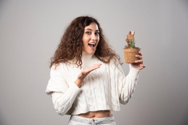 植物を持ってそれを指している若い女性。高品質の写真 無料写真