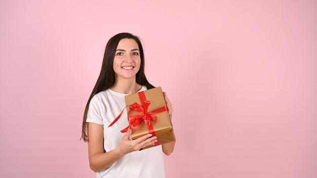 Молодая женщина, держащая улыбающийся подарок на розовом Premium Фотографии