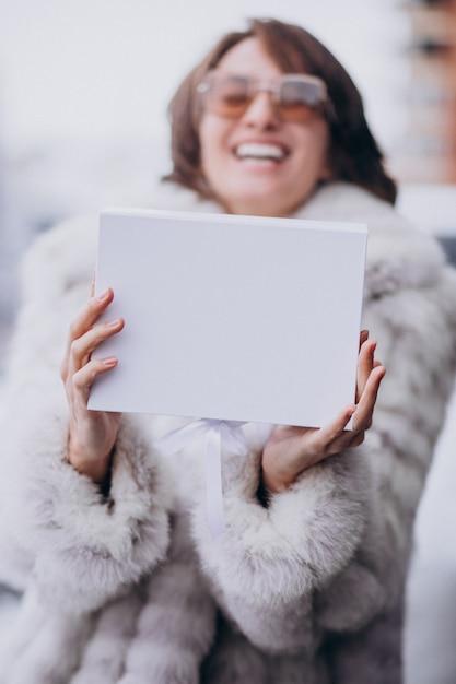야외에서 흰색 선물 상자를 들고 젊은 여자 무료 사진