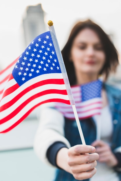 Young woman holding american flags Free Photo