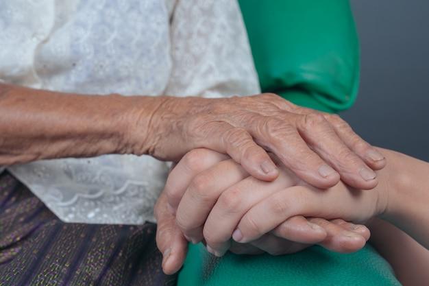 Молодая женщина, держащая руку пожилой женщины. Бесплатные Фотографии