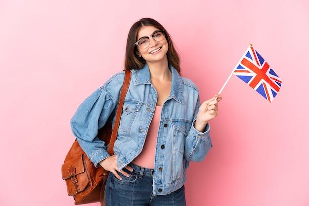 엉덩이에 팔을 포즈와 미소 핑크에 고립 된 영국 국기를 들고 젊은 여자 프리미엄 사진