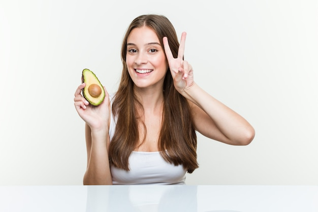 Young woman holding an avocado showing victory sign and smiling broadly Premium Photo