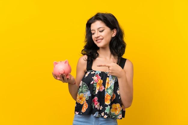 Young woman holding a big piggybank Premium Photo