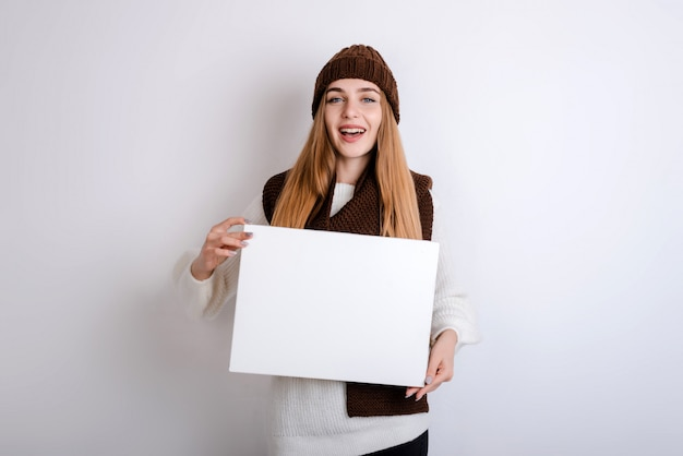 Young woman holding a blank sign in front oh her face Premium Photo