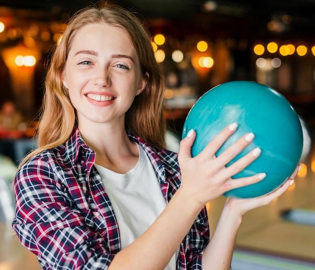 Giovane donna che tiene la palla da bowling Foto Gratuite