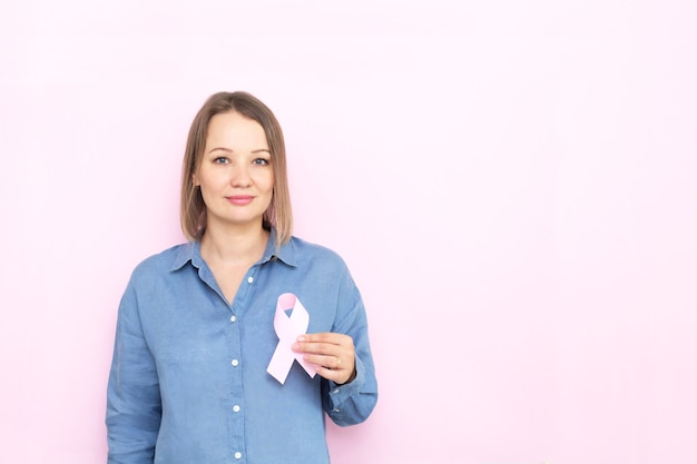Young woman holding brest cancer ribbon over pink background. Premium Photo