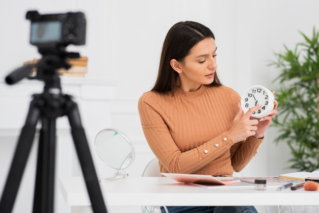 Young woman holding a clock on camera Free Photo