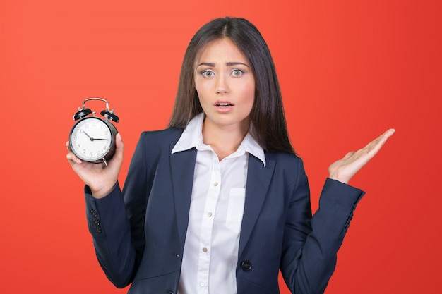 Young woman holding a clock. time management concept. Premium Photo