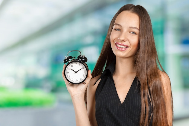 Young woman holding a clock Premium Photo
