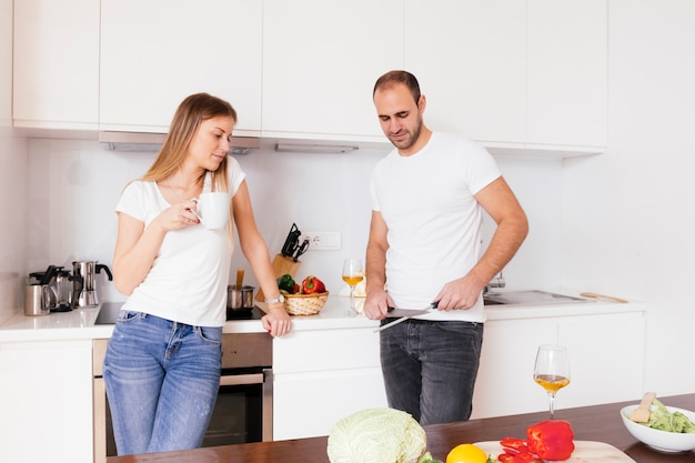 Young woman holding coffee cup in hand looking at her husband sharpening the knife Free Photo