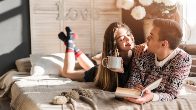 Young woman holding coffee cup in hand looking at man lying on bed Free Photo