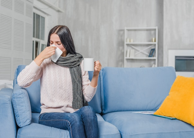 Young woman holding coffee mug suffering from cough Free Photo