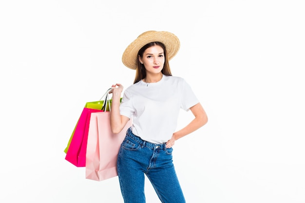 Young woman holding colorful bags isolated on white wall Free Photo