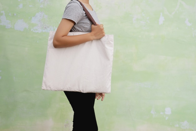 Young woman holding cotton bag on wall background. eco concept Premium Photo