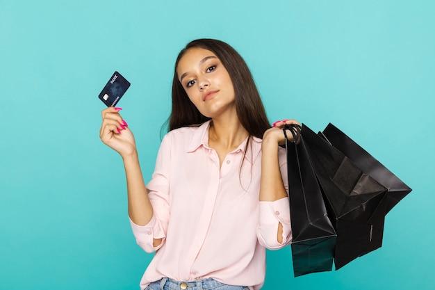 신용 카드와 검은 가방을 들고 웃 고 젊은 여자. 검은 금요일 개념. 프리미엄 사진