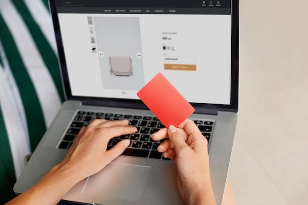 クレジットカードを保持しているとラップトップに入力してオンラインショッピングホームコンセプトの若い女性。インターネットバンキング、お金を使う Premium写真