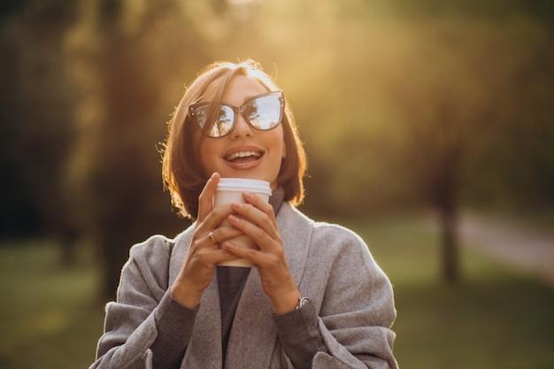 Молодая женщина, держащая чашку теплого кофе в парке Бесплатные Фотографии