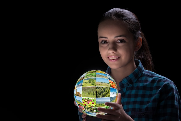Young woman holding earth with nature photos Premium Photo