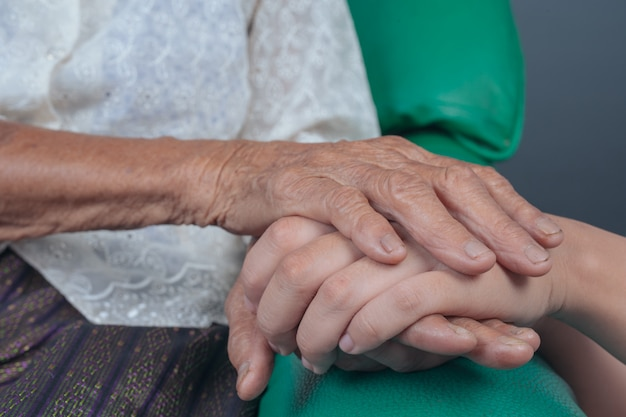 Young woman holding an elderly woman's hand. Free Photo