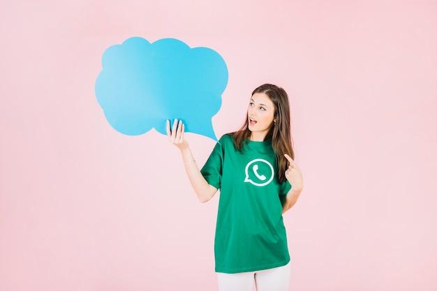 Молодая женщина, держащая пустой синий пузырь речи над розовым фоном Бесплатные Фотографии