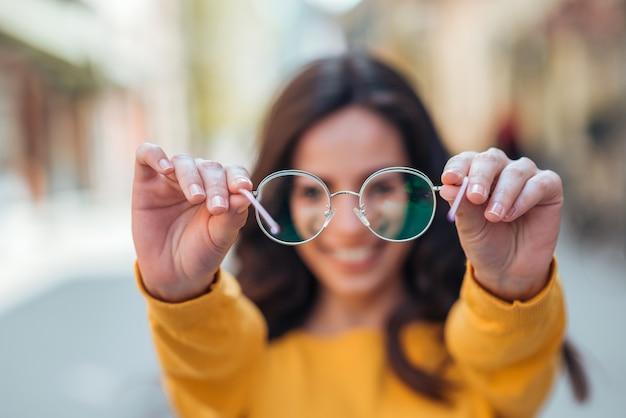 Young woman holding eyeglasses toward camera outdoors. Premium Photo