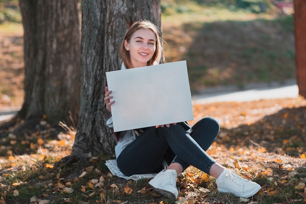 Young woman holding a frame with mockup Free Photo