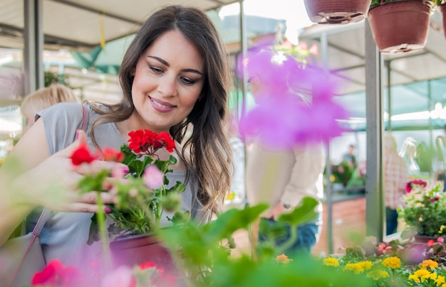 Young woman holding geranium in clay pot at garden center. young woman shopping flowers at market garden centre Free Photo