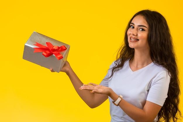 赤の弓とギフトボックスを保持している若い女性 無料写真
