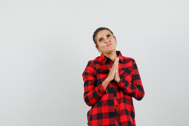 젊은 여자는 체크 셔츠에 제스처를기도하고 희망을 찾고 손을 잡고. 전면보기. 무료 사진