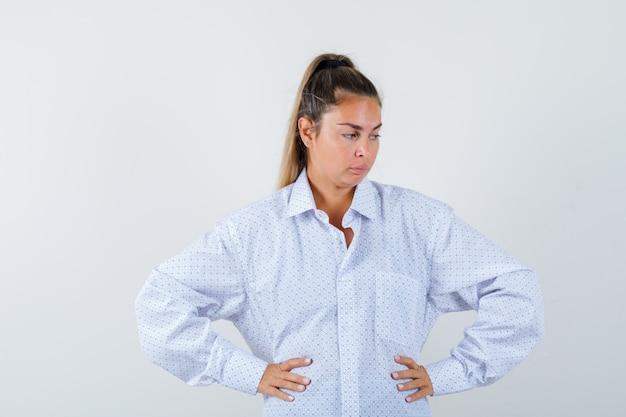 腰に手をつないで、白いシャツで何かを考えて、物思いにふける若い女性 無料写真