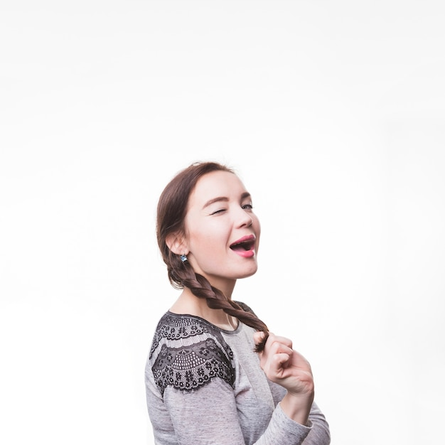 Young woman holding her braid blinking on white background Free Photo