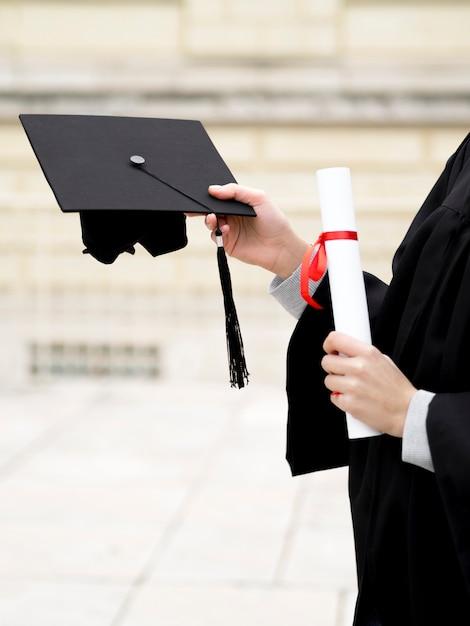 彼女の卒業の帽子を保持している若い女性 Premium写真