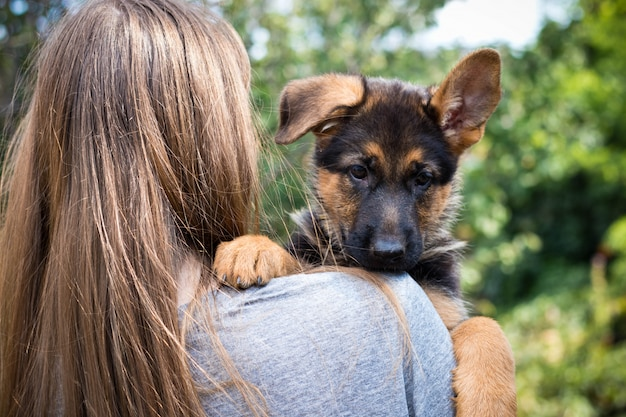 Young woman holding her puppy on shoulder Premium Photo