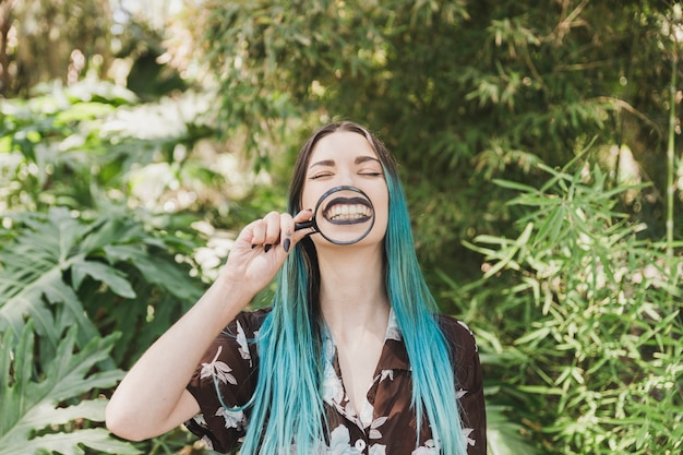 Young woman holding magnifying glass in front of her mouth Free Photo