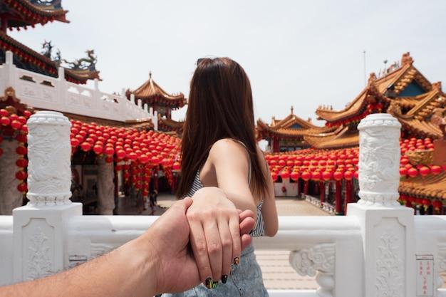 Young woman holding man hand travel in thean hou temple in kuala lumpur, malaysia Premium Photo