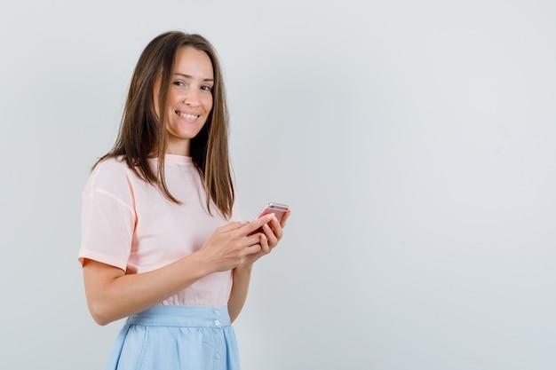 Tシャツ、スカート、陽気に見える携帯電話を保持している若い女性。正面図。 無料写真